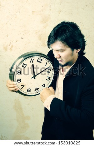 angry asian businessman boxing the clock