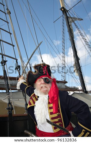 Angry bearded pirate captain in colorful traditional costume stands on board ship and waves his sword. Schooner rigging and blue sky in background, vertical layout.