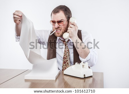 Angry bearing teeth chief of police at desk talking into landline phone while reading documents