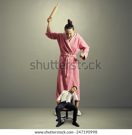 angry big wife with rolling pin screaming at lazy small husband in the grey room