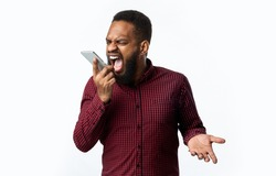 Angry Black Guy Shouting At Smartphone Talking By Phone Standing Over White Studio Background. Anger, Negative Emotion. Discontented Customer Having Quarrel By Cellphone