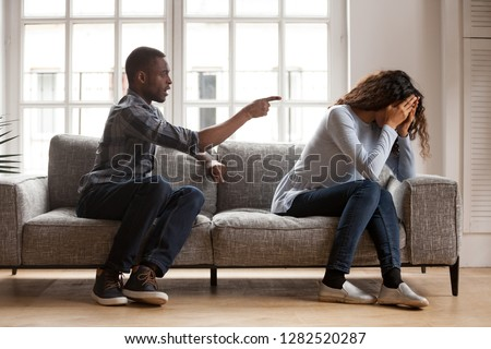 Angry black husband arguing yelling blaming upset wife of problems, jealous distrustful dominant african american boyfriend controlling shouting at sad girlfriend, quarrelling family fight at home Stockfoto ©