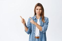 Angry blond girl feel unfair and displeased, pointing at upper left corner and frowning, condemn something bad or upsetting, standing against white background