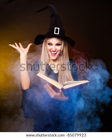 angry  blond witch with a book and her hands and clouds of blue smoke around her conjuring, against black and yellow background - stock photo