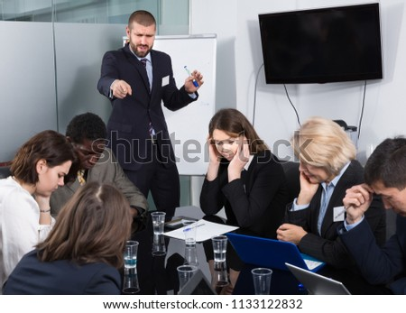 Angry boss berating his subordinates pointing out shortcomings and misses in work