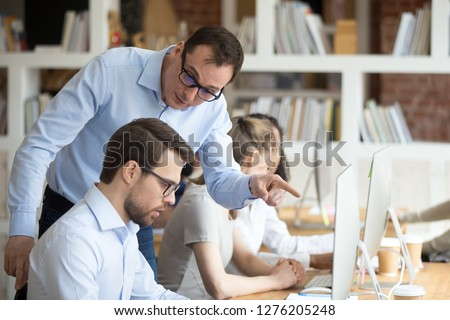 Angry boss criticizing scolding sad male employee for computer mistake incompetence at workplace, mad leader reprimanding rebuking shouting at subordinate lazy worker blaming of bad work in office