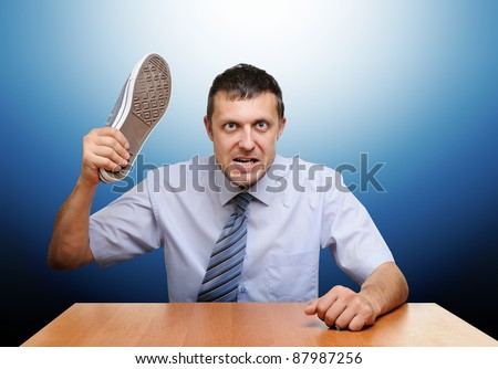 Angry boss knocks shoes on the table