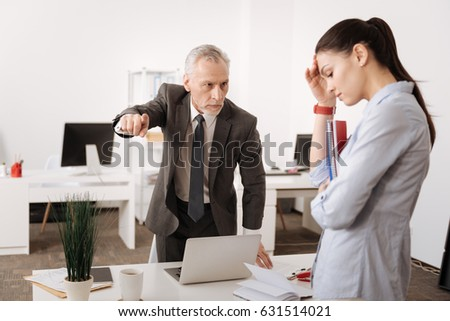 Angry boss standing opposite his secretary #631514021