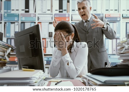 Angry boss yelling at his young employee, she is stressed and feeling frustrated: bullying boss and mobbing concept Stockfoto ©