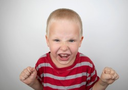 Angry boy screaming and hysteria on a white background. Four-year-old child shows child aggression