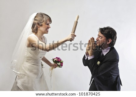 Angry bride waving threateningly a rolling pin against her husband