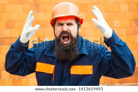 Angry builder. Incident at a construction site. Safety rules for builders. Bearded man in helmet on the construction of a new building. #1413619493
