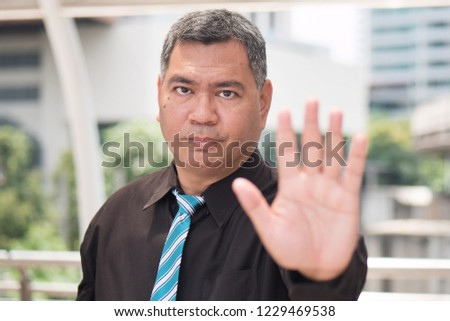 angry business man saying no. portrait of angry, upset asian businessman showing stop, halt hand gesture. 50s old southeast asian man model