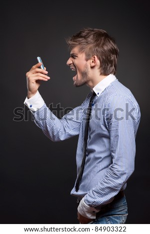 Angry business man screaming on phone over black background