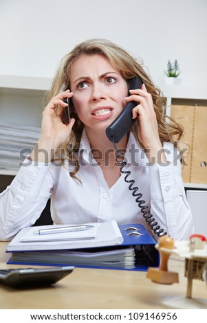 Angry business woman in her office on two phones at the same time