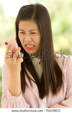 Angry business woman using cell phone.