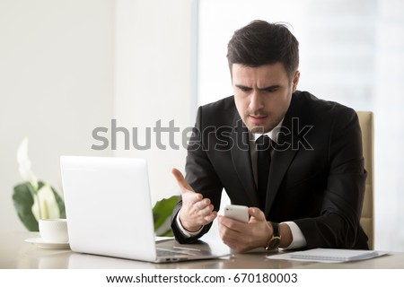 Angry businessman annoyed with phone call while working on laptop at office, receiving bad news on smartphone, irritated by spamming message, mobile not working, battery needs recharge, broken cell