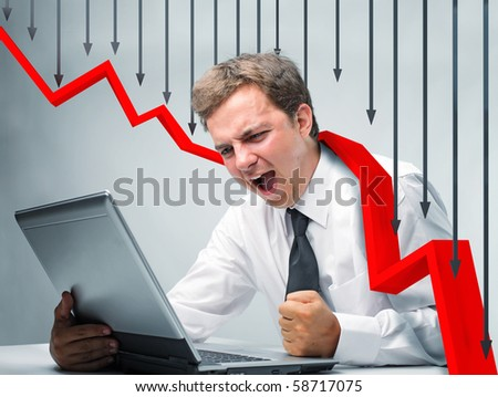 angry businessman at laptop and falling red 3d business stat