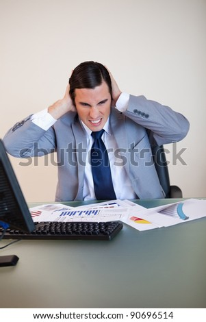 Angry businessman covering his ears