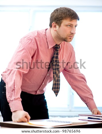 Angry businessman leans on the table