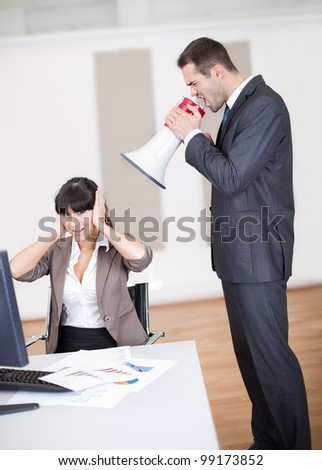 Angry businessman screaming at employee at the office in megaphone