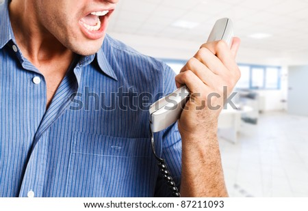 Angry businessman screaming at the phone