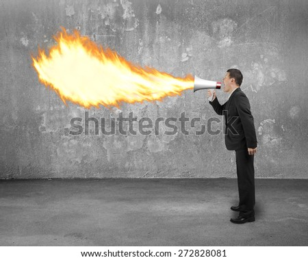 Angry businessman screaming into megaphone spitting fire flame with concrete indoor background