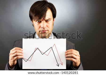 Angry businessman showing a falling graph of stock market against gray