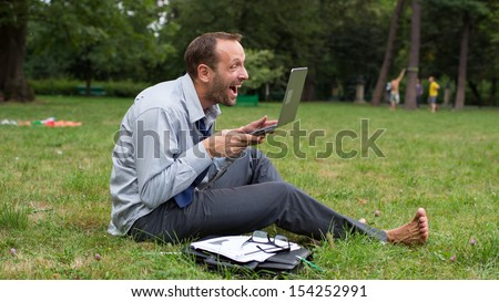 Angry businessman sitting on a grass with laptop.