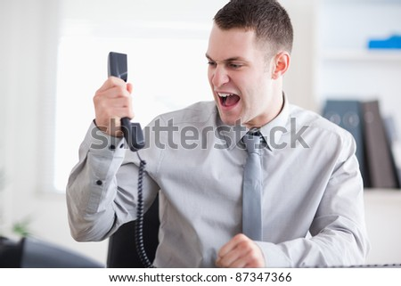 Angry businessman yelling at the phone