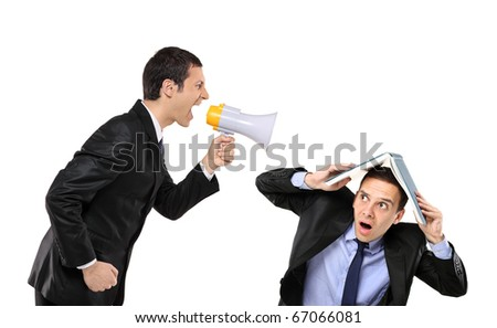 Angry businessman yelling via megaphone to a man who is covering his head with book