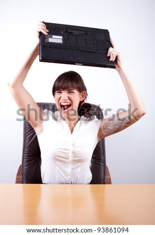 Angry businesswoman about to throw her laptop. Office rage series.
