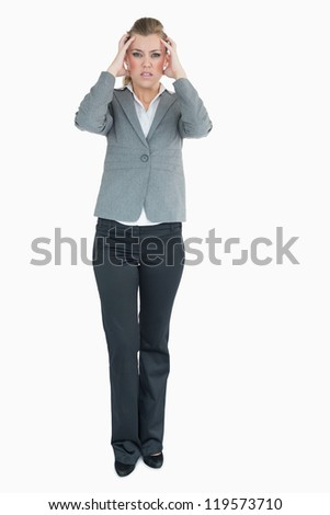 Angry businesswoman holding her hands to her head