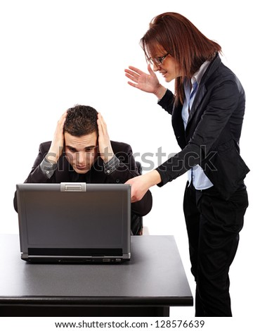 Angry businesswoman screaming at her employee and showing the mistakes on a laptop