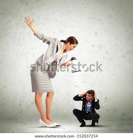Angry businesswoman with megaphone shouting at colleague