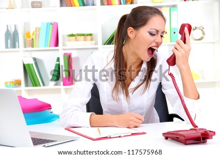 angry businesswoman with phone at office