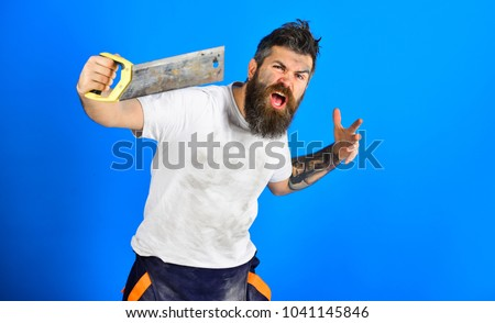Angry carpenter concept. Guy with beard covered with dust. Builder, worker, carpenter, handyman holds saw or hacksaw, blue background. Man with shouting expression in dirty shirt, holds handsaw.
