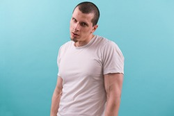Angry caucasian man in white t-shirt dangerously and suspiciously looks at the camera on the light blue background. Serious. Seriously. Sideways glance. Annoyed. Unhappy