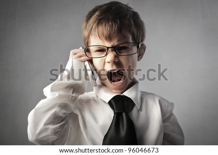 Angry child disguised as a businessman screaming on the mobile phone - stock photo