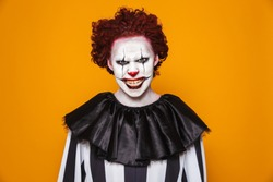 Angry clown man 20s wearing black costume and halloween makeup looking at camera isolated over yellow background