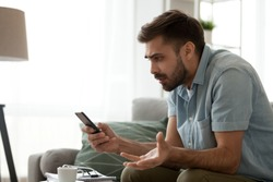 Angry confused man holding discharged phone annoyed by spam message, missed call or bad mobile signal looking at smartphone, mad male customer frustrated by cellphone problem receiving bad news