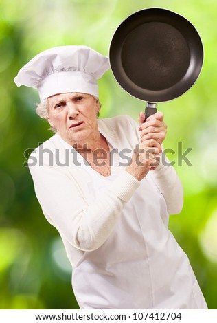 angry cook senior woman trying to hit with a pan against a nature background
