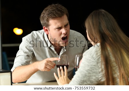 Angry couple arguing furiously in a bar at night #753559732