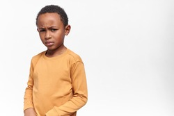 Angry dark skinned little boy in yellow sweatshirt frowning eyebrows, being stubborn. Displeased African child posing isolated against white studio wall background with copy space for your information