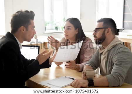 Angry deceived couple customers disputing about mortgage loan or real estate problem with realtor, lawyer or architect, clients having claim about house construction, bad contractor and fraud concept