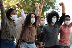 Angry demonstrators in face masks protesting on the street. International group of strikers raising clenched fists up, fighting against racism or defending animal rights, protesting against quarantine