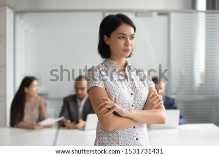 Angry displeased Asian businesswoman with arms crossed standing in office, young female employee has problem at work, feeling tension and pressure, discrimination, bad relations with colleagues
