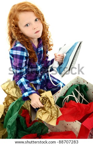 Angry dissappointed girl child receiving an iron as a gift.  Over white background.