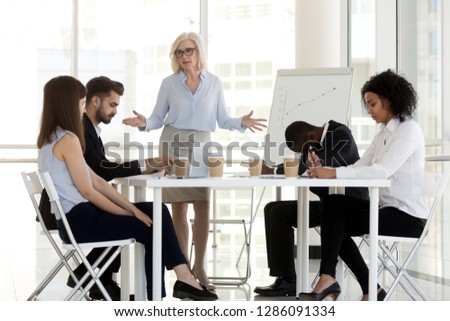 Angry dissatisfied company owner or team leader mature businesswoman scold young diverse multiracial incompetent workers. Multi-ethnic employees feel guilty made mistake which cause serious losses