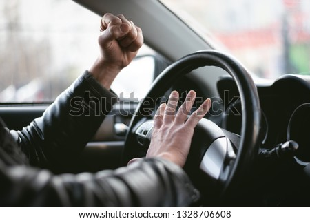 Angry driver is honking and is yelling by sitting of a steering wheel. Road aggression concept. Traffic jam. #1328706608
